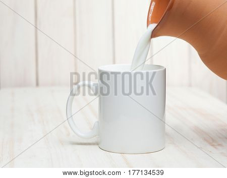 Milk is poured into a cup of pitcher on white background wooden table