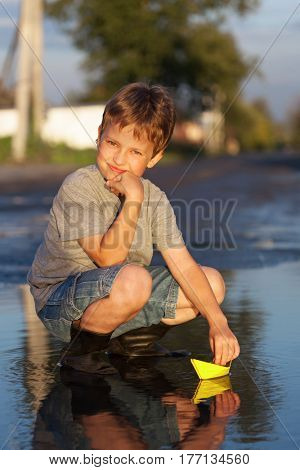 boy play with autumn paper ship in water, chidren in park play with boat in river