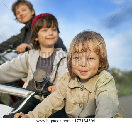 three brothers ride bikes (composition with copy space)