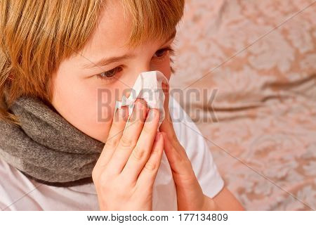 Health and medicine concept - little boy is sick with the flu. The boy wipes his nose with a tissue.