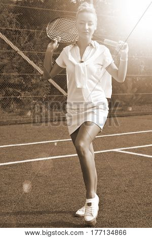 Happy girl stands with racket on court at sunny summer