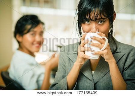 Smiling businesswoman enjoy drinking coffee in office