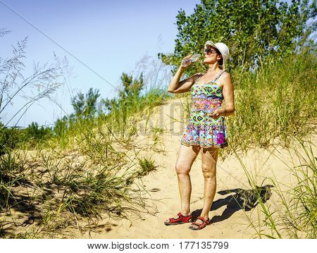 Woman is drinking water while hiking in the dunes in Northern Michigan