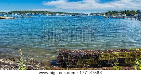 Lobster traps wait along the shore of West Boothbay Harbor at Cape Newagen on the coast of Maine.
