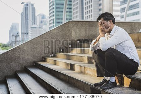 Young depressed businessman sitting on the stairs