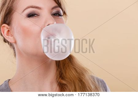 Sweets and candies. Fun and joy. Young blonde girl having fun with sweet food. Joyful woman chewing white gum making balloon.