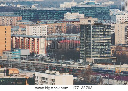 Close-up shooting from top of metropolitan city: several tracks of railway with suburban electric train residential and business office buildings and districts multiple facades Moscow Russia