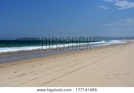Belmont Nine Miles beach on a sunny day in summertime. Blacksmith Point in the background (Central Coast NSW Australia).