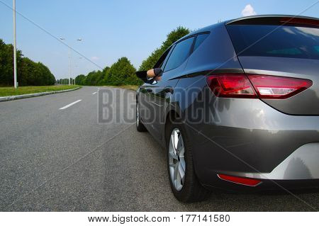 Car on asphalt road in nature. Man hand relaxing and enjoying road trip and sunny.