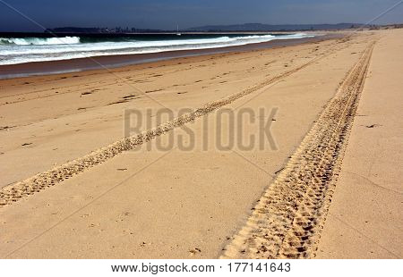 Horizontal landscape of the beach with tyre track in the foreground and dramatic clouds (Belmont Nine Miles Beach NSW Australia)