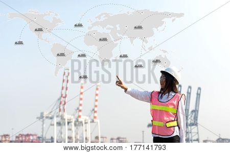The women engineer working with container Cargo freight ship in shipyard at dusk for Logistic Import Export background map earth for cargo freight ship