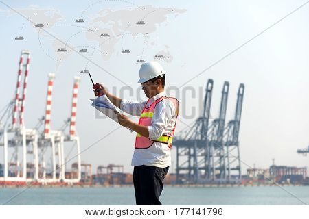 The man engineer working with container Cargo freight ship in shipyard at dusk for Logistic Import Export background map earth for cargo freight ship