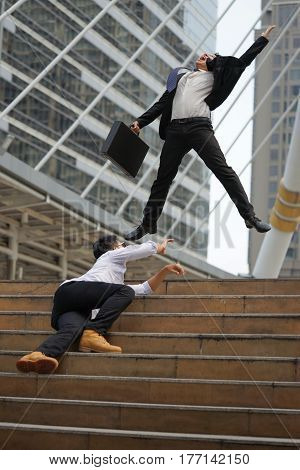 Businessman in suit jumping holding document bag feeling happy when he success and another businessman tries to reach for success as well.
