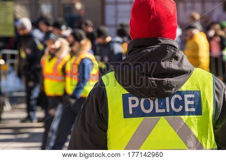 Montreal Canada - 19 March 2017: Rear view of a Policeman at St. Patrick's Day parade