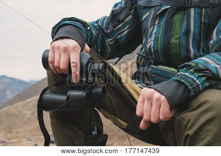 Large binoculars in the man's hand of a traveler who is in the mountains, close-up