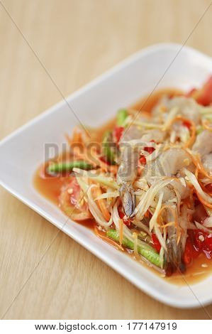 SOM TUMThai foods or papaya salad with fresh shrimp in spicy taste and is popular in thailand on wooden table background.