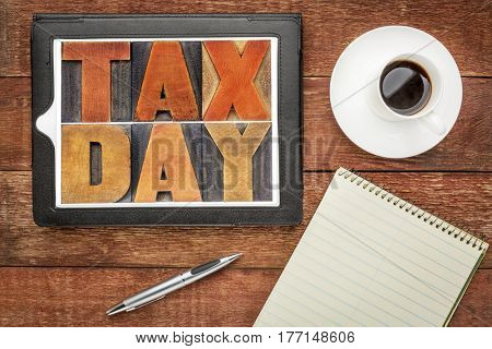 tax day word abstract in vintage letterpress wood type on a digital tablet with coffee and notebook