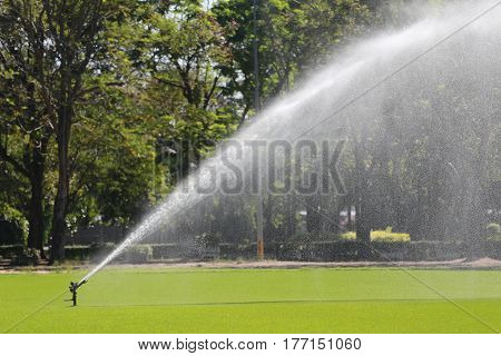 Sprinkler in Watering green lawn of golf courses in the morning.