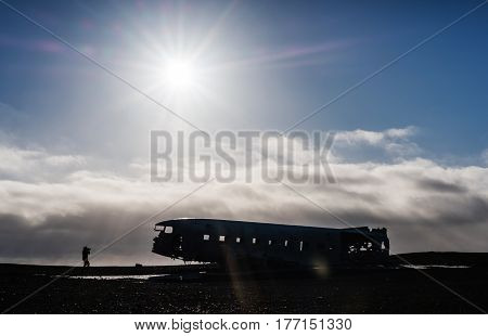 Wreck abandoned airplane with silhouette traveler taking a photo, with bright sunlight with flare effects