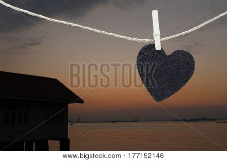 Black Heart hung on hemp rope on view sunset background and have copy space to manage the text you want.