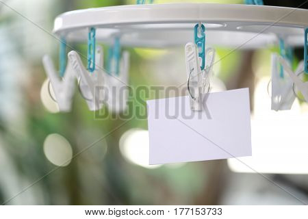 white paper notes hanging in a clothesline on green bokeh background.