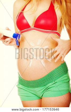 Pregnant woman applying sun cream on her belly