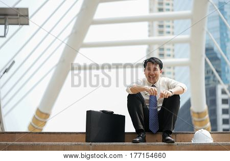 Businessman sit happily laughing at the ladder modern walkway middle town.