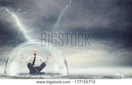 Businessman safely inside a sphere during a storm . Protect the financial and economic serenity