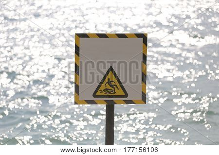 Warning labels of warning beware slippery in seaside area and have sea background.