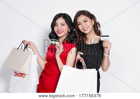 Two Happy Attractive Young Women With Creadit Card Holding Shopping Bags On White Background