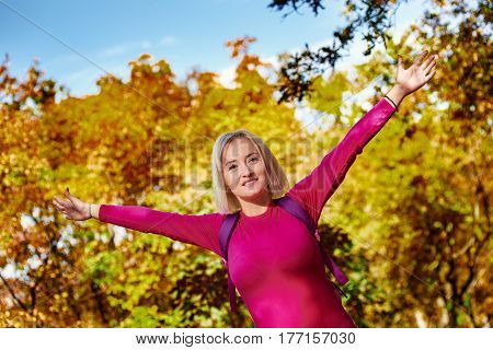 Portrait of pretty smiling sportswoman with raised hands in autumn forest