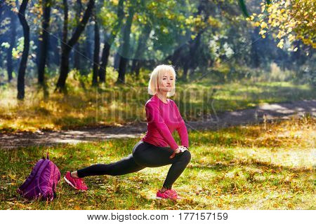 Pretty woman doing stretching exercises outdoor in park
