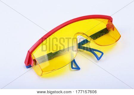 Orange earplug and safety glasses. Earplug to reduce noise on a white background