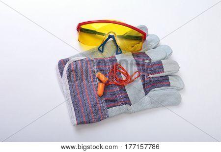 Orange earplug, safety glasses and glovs. Earplug to reduce noise on a white background