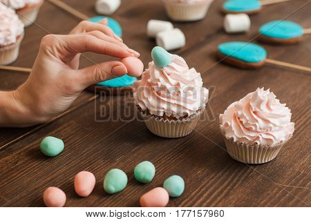 Masterclass of preparing decorated cupcakes with white cream on wooden table. Cookery arts.