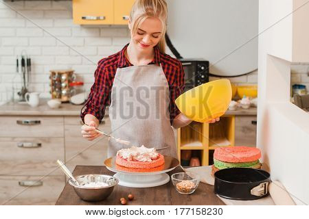 Woman preparing a sweet homemade cake on kitchen wooden table. Blogger, birthday celebration , small business, delivery of sweets , culinary craftsmanship, good housewife concept