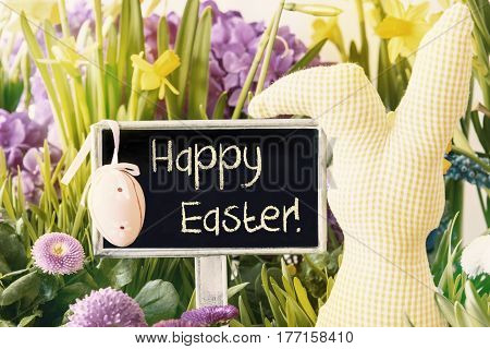 Sign With English Text Happy Easter. Spring Flowers Like Narcissus. Easter Bunny And Easter Egg As Decoration. Card For Seasons Greetings