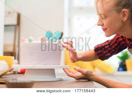 Girl makes a easter biscuit cake in the kitchen. Homemade cakes for selling. Happy chef making festive sweets. Culinary art, woman craftsmanship, good wife concept