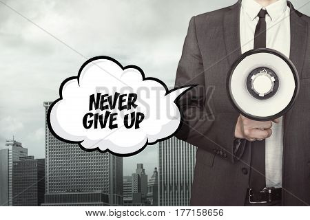Never give up text on speech bubble with businessman holding megaphone
