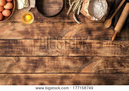 Baking ingredients on a wooden table with copy space. Flour eggs butter with a rolling pin
