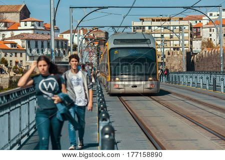 PORTO, PORTUGAL - MAR 10, 2017: Train of Porto Metro on Dom Luis iron Bridge in Old Town. The network has 6 lines and reaches seven municipalities within the metropolitan Porto area.