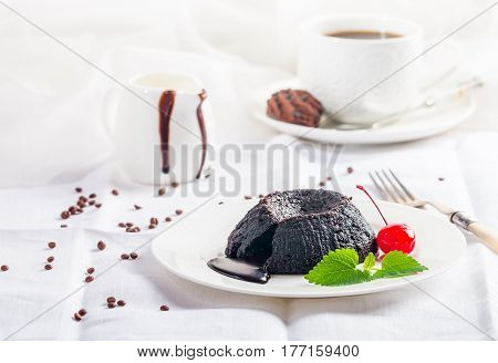 Hot chocolate pudding with fondant centre on white plate, close-up