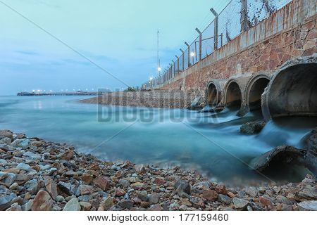 Drainage pipe with water flowing into the sea in the evening.