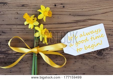 Label With English Quote It Is Always A Good Time To Begin. Yellow Spring Narcissus Or Daffodil With Ribbon. Aged, Rustic Wodden Background. Greeting Card For Spring Season