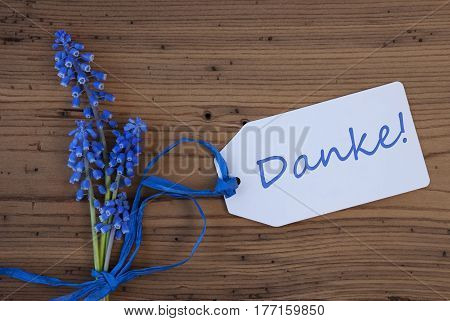 Label With German Text Danke Means Thank You. Blue Spring Grape Hyacinth With Ribbon. Aged, Rustic Wodden Background. Greeting Card For Spring Season