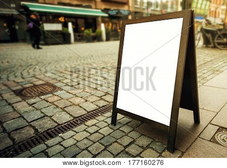 Blank restaurant advertising board as copy space on the street. Angled freestanding A-frame blackboard for mockup design.