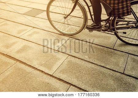 Unrecognizable female hipster person riding bicycle on city street retro toned monochromatic image