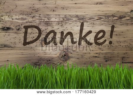 German Text Danke Means Thank You. Spring Season Greeting Card. Aged Wooden Background With Gras.