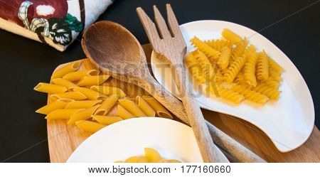 italian pasta and wood kitchen utensils displayed on a chopping board