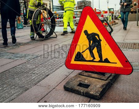 Road works sign on city street workers and pedestrians in the background